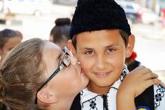 Unga flickan kysser pojken och kramar honom Arkivbild
