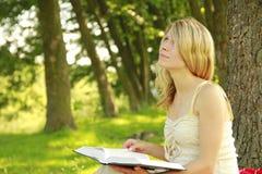 Unga flickan läser bibeln Arkivbilder