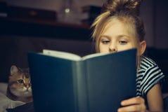 Unga flickan läser boken till en katt arkivfoton