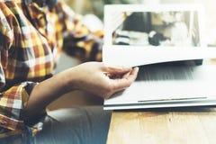 Unga flickan läser boken under frukosten och kaffe, kvinnliga händer som är nära upp bläddring till och med tidskriftsidor i hem  royaltyfria bilder