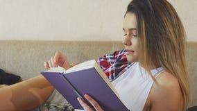 Unga flickan läser en bok arkivfoton