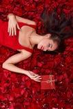 Unga flickan ligger i rosa kronblad som är hållande på gåvaasken och att se den royaltyfri bild