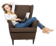 Unga flickan lyssnar musik på stol royaltyfri fotografi