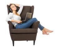 Unga flickan lyssnar musik på stol arkivbilder