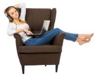 Unga flickan lyssnar musik på stol arkivbild