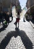 Unga flickan med ängel påskyndar på Lviv gator royaltyfria foton