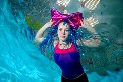 Unga flickan med den stora pilbågeclownen på huvudet simmar i pölen som är undervattens- och ser kameran Stående den konstnärliga Royaltyfri Bild