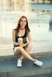 Unga flickan med en drink i hennes händer sitter på bakgrunden av a Royaltyfri Fotografi