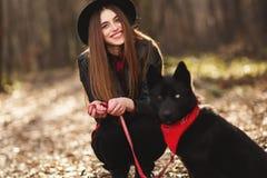 Unga flickan med en hund som g?r i h?sten, parkerar Flickan har en h?rlig svart hatt arkivfoto