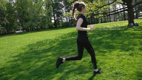 Unga flickan med en lång flätad tråd har kört i parkera Ung kvinna som joggar i sommaren, ultrarapid stock video