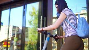 Unga flickan med en telefon i hennes hand vänder på den elektriska sparkcykeln och sidorna