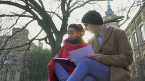 Unga flickan med grabben talar om bildande material nära universitet stock video