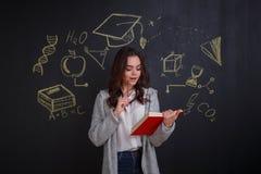 Unga flickan med intresse läser en bok som står bredvid en whiteboard med en bild av vetenskap arkivbild