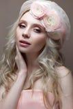 Unga flickan med krullning i en hatt med skyler Härlig modell med en krans av blommor på hennes huvud Royaltyfri Bild