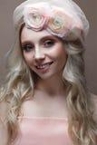 Unga flickan med krullning i en hatt med skyler Härlig modell med en krans av blommor på hennes huvud Royaltyfria Bilder