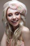 Unga flickan med krullning i en hatt med skyler Härlig modell med en krans av blommor på hennes huvud Arkivbilder