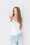 Unga flickan med långt hår som coolt ler och visar ` för gest`, showutvärdering av den kosmetiska produkten, rekommenderar skönhe royaltyfri bild