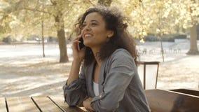 Unga flickan med mörkt lockigt hår som använder telefonen i en stad, parkerar arkivfilmer