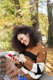 Unga flickan med m?rkt lockigt h?r som anv?nder telefonen i en stad, parkerar arkivbilder