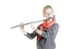 Unga flickan med röda hår- och fräknelekar blåser flöjt Royaltyfri Foto