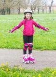 Unga flickan med rullskridskor i parkerar royaltyfri fotografi