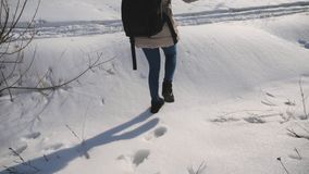Unga flickan med ryggsäcken går i snöig skogkvinna går och lämnar spår på snön för ligganderussia för 33c januari ural vinter tem arkivfilmer