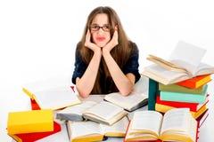 Unga flickan önskar inte att studera, henne är trött och att placera i surround Arkivfoto