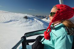 Unga flickan på stolelevator på skidar semesterorten arkivbilder