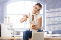 Unga flickan på telefonen som ser, spikar att le Arkivfoton