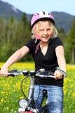 Unga flickan passerar cykeln Royaltyfria Bilder