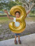Unga flickan petar hennes huvud till och med en metallisk guld- ballong för stort antal tre royaltyfria foton