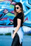 Unga flickan poserar i en härlig vårdag framme av grafitti på väggen i bakgrund Arkivfoto