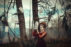 Unga flickan poserar i en röd klänning med den idérika frisyren royaltyfri foto
