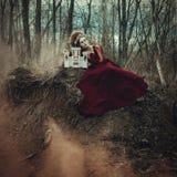 Unga flickan poserar i en röd klänning med den idérika frisyren royaltyfri bild