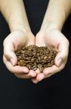 Unga flickan räcker hållande kaffebönor Royaltyfria Bilder