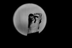 Unga flickan reeled hår runt om näsan; I ljuset av projektorn Fotografering för Bildbyråer