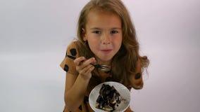 Unga flickan rymmer en platta med ett stycke av chokladkakan och tycker om smaken stock video