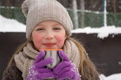 Unga flickan rymmer i hennes hand ett kopp tetermoslock utomhus på en frostig dag arkivfoton