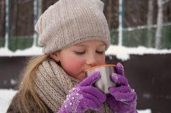 Unga flickan rymmer i hennes hand ett kopp tetermoslock utomhus på en frostig dag arkivbilder