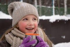 Unga flickan rymmer i hennes hand ett kopp tetermoslock utomhus på en frostig dag royaltyfri foto