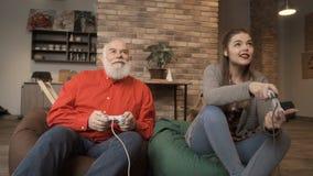 Unga flickan segrar videospelet i konkurrens med hennes farfar stock video
