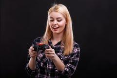 Unga flickan ser fascinatingly panelen av den modiga styrspaken På en svart bakgrund Arkivfoto
