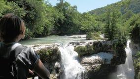 Unga flickan ser till den lilla vattenfallet, Georgia, Martvili stock video