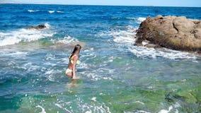 Unga flickan simmar i den lösa steniga stranden arkivfilmer