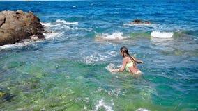 Unga flickan simmar i den lösa steniga stranden stock video