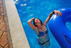 Unga flickan simmar i pölen med en rubber cirkel Hon har kastat tillbaka huvudet och sköljer hår Arkivbild