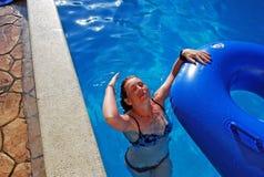 Unga flickan simmar i pölen med en rubber cirkel Hon har kastat tillbaka huvudet och sköljer hår Royaltyfri Foto