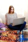 Unga flickan sitter arbete med en hemmastadd bärbar dator Royaltyfri Bild
