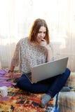 Unga flickan sitter arbete med en hemmastadd bärbar dator Royaltyfri Foto