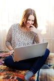 Unga flickan sitter arbete med en hemmastadd bärbar dator Royaltyfria Foton
